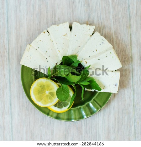 Green plate with tofu, lemon and mint on a wooden background - stock photo
