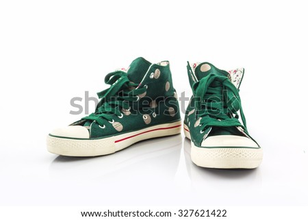 Green polka dot canvas shoe on white background.