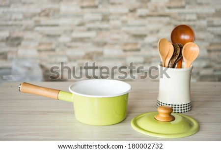 green pot on wooden table - stock photo