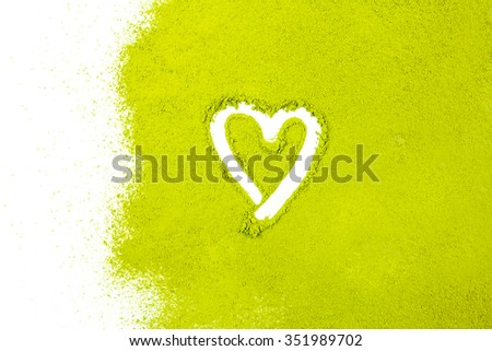 green powder forming heart shape surface close up isolated on white background - stock photo