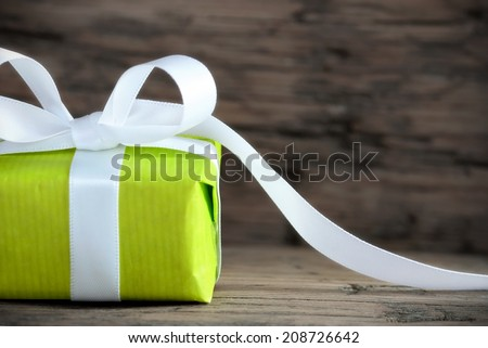 Green Present on Wood with White Ribbon and Copy Space - stock photo