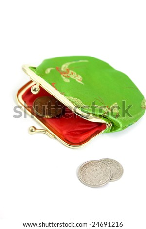Green purse with some coins in front of it - stock photo