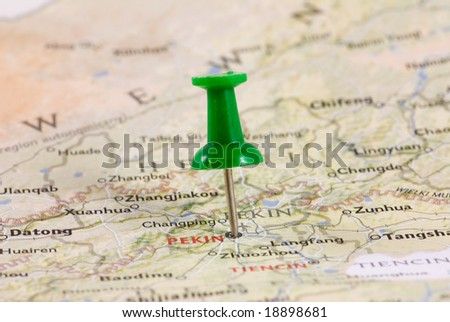 Green pushpin marking a location on a map - stock photo