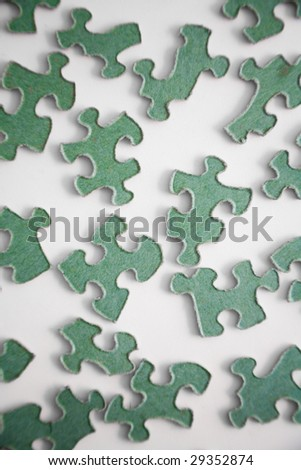 Green puzzle pieces against a white background. - stock photo