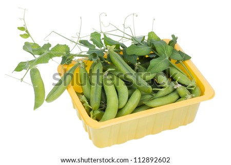 Green raw real pea in yellow plastic box container  isolated. Selective focus - stock photo