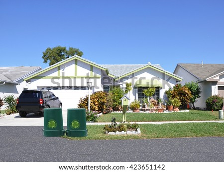 Green recycle, reuse, reduce, trash container Beautiful Suburban Ranch Home Sunny residential neighborhood Clear Blue Sky USA - stock photo