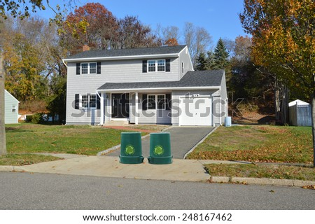 Green recycle, reuse, reduce, trash container Suburban Gray High Ranch home autumn day residential neighborhood clear blue sky day USA - stock photo