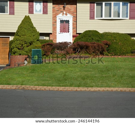 Green recycle, reuse, reduce, trash container Suburban High Ranch brick landscaped home with cobble stone curb sunny autumn day residential neighborhood USA - stock photo