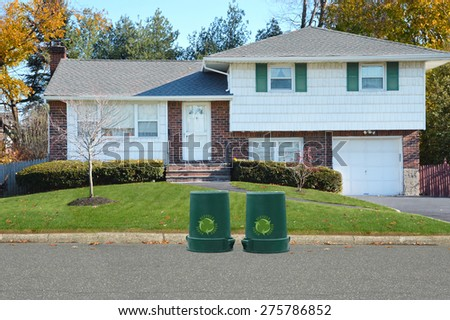 Green recycle, reuse, reduce, trash container Suburban High Ranch Home Twilight Autumn Day Residential Neighborhood USA - stock photo