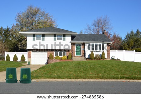 Green recycle, reuse, reduce, trash container Suburban Ranch home sunny clear blue sky residential neighborhood USA - stock photo