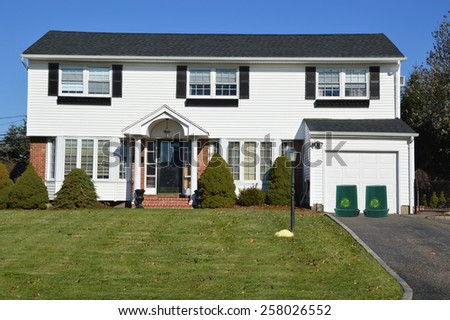 Green recycle, reuse, reduce, trash containers Suburban White and Black McMansion home sunny residential neighborhood clear blue sky day USA - stock photo