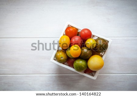 Green, red and yellow Heirloom tomatoes in a white container on a white good background with a light vignette - stock photo