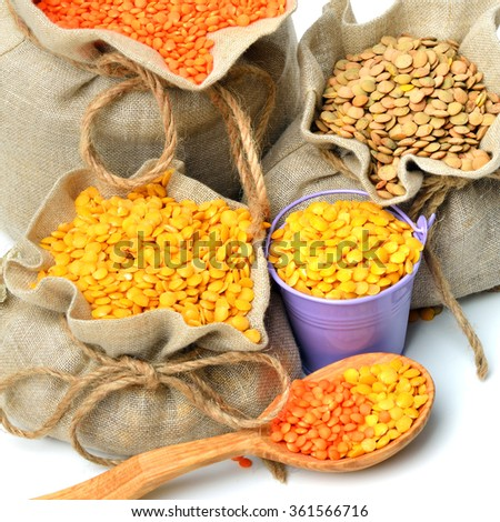 green, red and yellow lentils in the sacks and spoon wooden isolated on white background - stock photo
