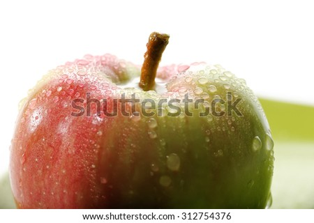 Green Red apple in drops of water on a white background, macro - stock photo