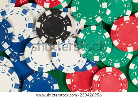 Green, red, blue, white and black Playing Poker Chips in a green background