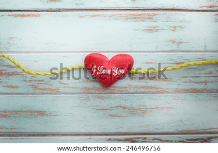 green ribbon tape and heart on vintage wooden background