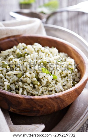 Green rice with herbs in wooden bowl - stock photo