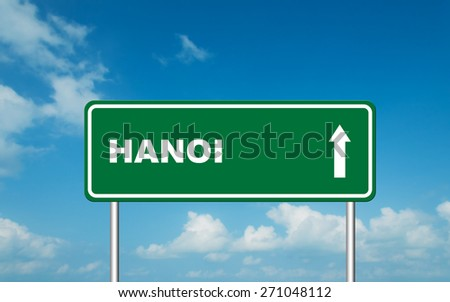Green road sign board with straight direction to Hanoi with sky background - stock photo