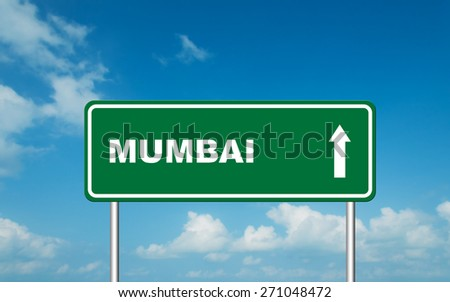 Green road sign board with straight direction to Mumbai with sky background - stock photo