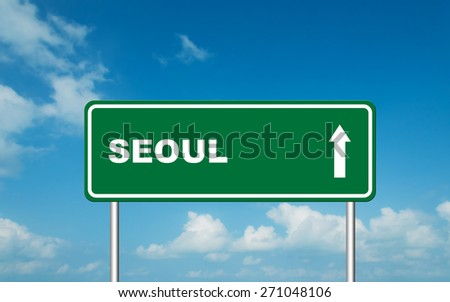 Green road sign board with straight direction to Seoul with sky background - stock photo