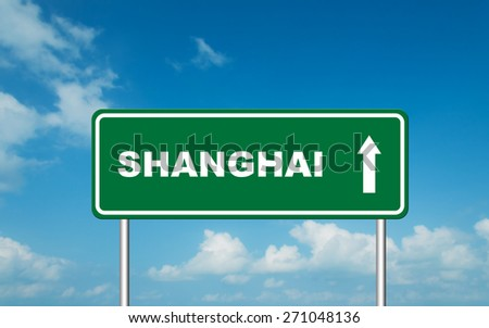 Green road sign board with straight direction to Shanghai with sky background - stock photo