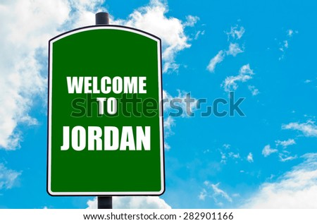 Green road sign with greeting message WELCOME TO JORDAN isolated over clear blue sky background with available copy space. Travel destination concept  image - stock photo