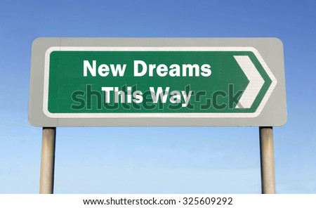 Green road sign with the message of a New Dreams This Way concept against a blue sky background