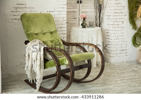 Green rocking chair on a background of a brick wall in the interior of ...