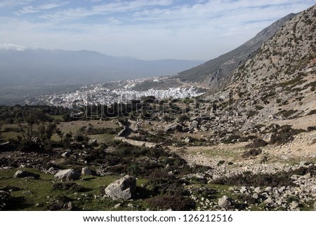 Green rocky mountains surround the Hidden fortress city of Chefchaouen, Morocco.