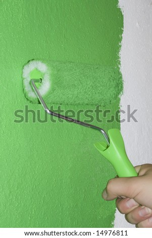 Green roller coloring on white surface - stock photo