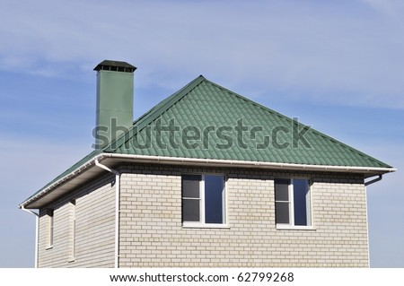 Green roof of new white brick house on blue sky background - stock photo