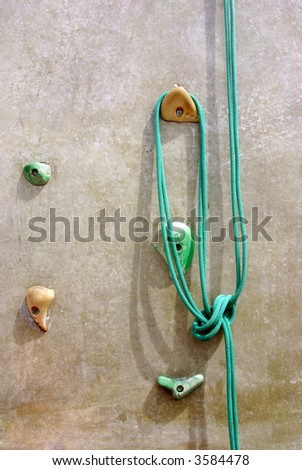 Green rope with a knot hanging in a climbing wall. - stock photo