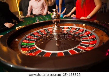 green roulette table with colored chips ready to play - stock photo