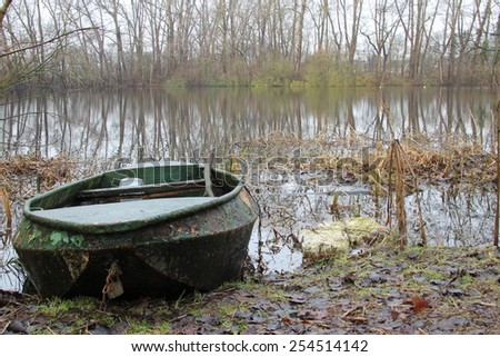 green rusty rowing boat on a lake - stock photo