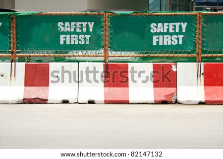 Green safety first signs and road concrete barriers - stock photo