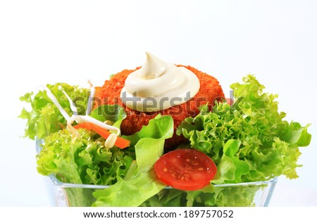 Green salad with fried breaded cheese and mayonnaise - stock photo