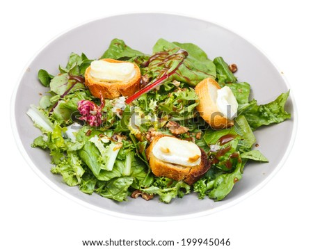 green salad with goat cheese and toasted bread on plate isolated on white background - stock photo