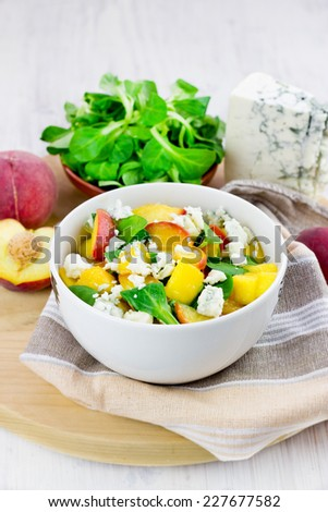 Green salad with grilled peaches, gorgonzola cheese and corn salad leaves, selective focus - stock photo