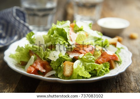 Green salad with salmon, parmesan cheese and fried bread