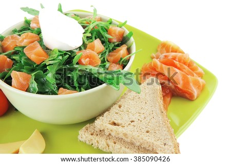 green salad with smoked salmon and bread on plate