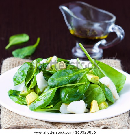 Green salad with spinach, white fish and avocado with sauce, tasty dish - stock photo