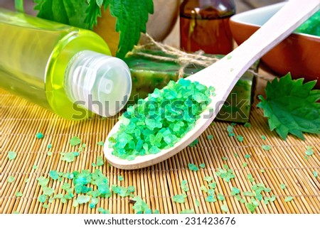 Green salt, shampoo, oil, gel, soap with nettles in a mortar on a wooden boards background - stock photo