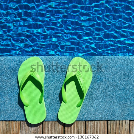 Green sandals by a swimming pool - stock photo