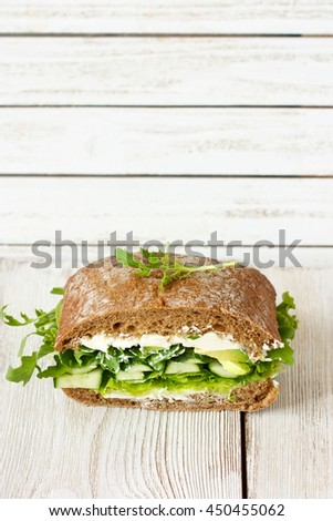 Green sandwich with soft cheese, avocado and fresh cucumber.