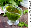 Green sauce marinade from herbs oregano, parsley, oil, traditional chimichuri in glass sauce-boat - stock photo