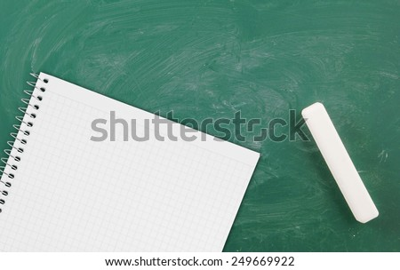 Green school board with chalk and blank checked note paper for text - stock photo