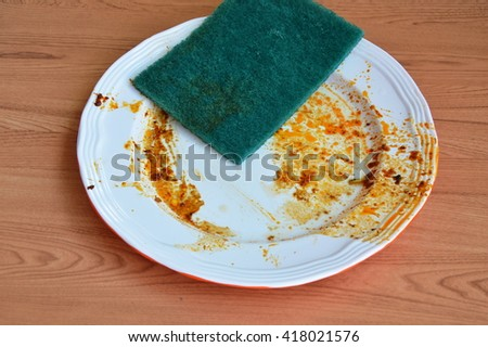 green scrub sponge wash food stain on white dish - stock photo