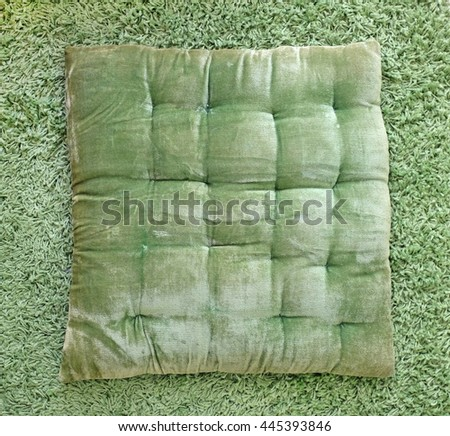 Green Seat Pad on green carpet Background - stock photo