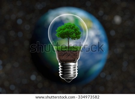 Green seedlings in a light bulb alternative energy concept, against a blurred background of planet Earth in space - stock photo