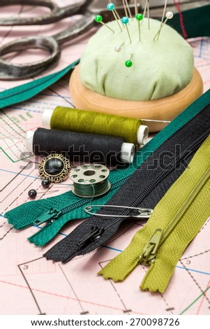Green sewing accessories: zippers, threads, buttons on pattern cutting - stock photo